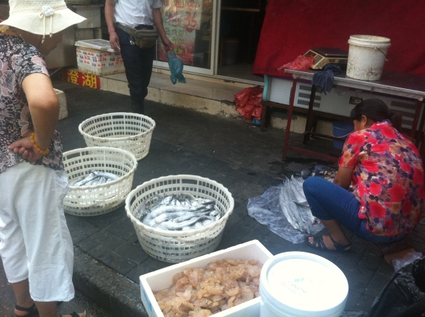 "Shanghainese do most of their grocery shopping in the mornings, buying everything from lettuce to fish for their meal that evening. This fish, or ""dai yu"" is apparently quite delicious according to the woman in the red who attempted to sell her product to me, the ""laowai."""