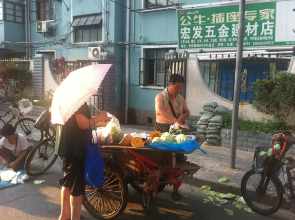 Even in the wee hours of the morning, the Shanghai women don't want to get any unwanted sun while they do their grocery shopping. This woman proceeded to buy quite a few veggies, all whilst clutching onto her daintily pink umbrella.